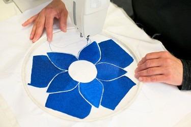 Plná plošná výšivka květinového heraldického motivu. Precizní ruční klad stehů do napnutého podkladového sametu u tohoto motivu zabere vyšívačce celý pracovní den.