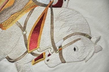 Detail řemeslné výšivky repliky praporu. Vyšívačka vždy sama rozhoduje o kladu každého jednotlivého stehu svými zručnými pohyby a ručním posunem bubínku, včetně častého střídání barev vyšívacího hedvábí, které je zárukou originality a umělecké kvality.