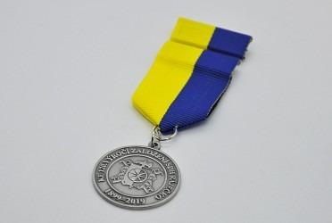 Pamětní medaile pro hasiče se závěsnou stuhou a klopovou stužkou.
