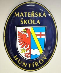 Smaltovaný ovál s obecním znakem a označením budovy mateřské školy