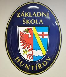 Smaltovaný ovál s obecním znakem a označením budovy základní školy