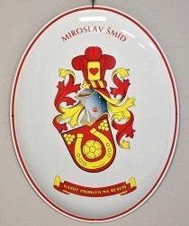 Smaltovaný ovál, který nese osobním znak s firemní symbolikou.