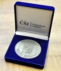 Záslužná medaile uložená v dárkové krabičce.
