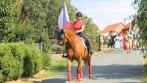 V čele průvodu šel šampion mezi koňmi ve státních barvách s vlajkonoškou, která nesla symbol české státnosti – českou státní vlajku.