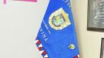 Vyšívaný policejní prapor vyvěšený na dvoudílné žerdi